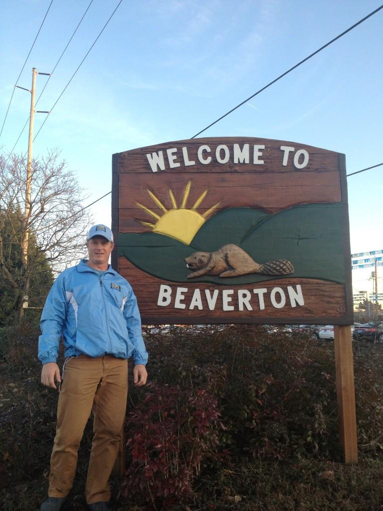 man standing in front of beaverton oregon sign