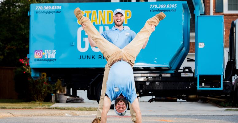 two junk removal experts standing in front of truck in highland park texas