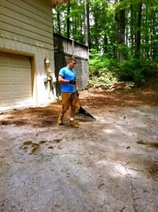 man sweeping driveway