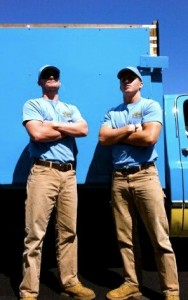 two men standing in front of a stand up guys junk removal truck