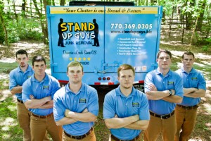 stand up guys junk removal crew standing in front of a truck