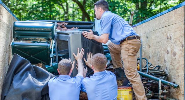 men loading junk into truck