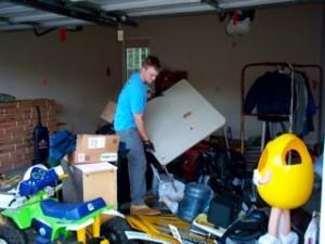 man holding junk in a garage