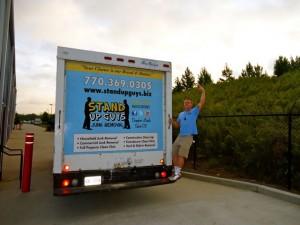 man hanging off junk truck