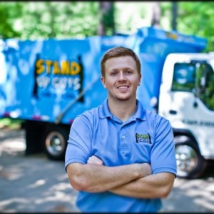 casey walsh, owner of stand up guys junk removal in from of a dump truck
