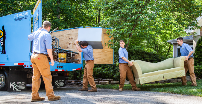 three men hauling junk furniture