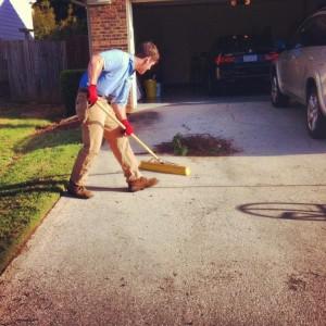 man sweeping up driveway