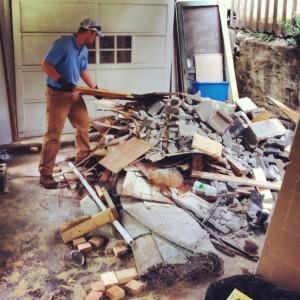 man removing pile of construction debris