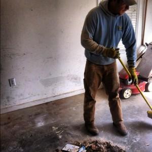 man sweeping up kitchen debris