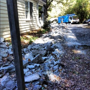 concrete debris on driveway with junk truck in background