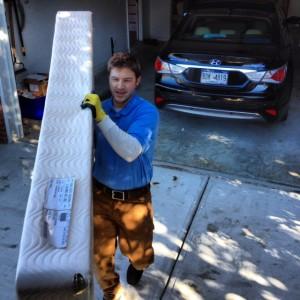 man carrying a junk mattress